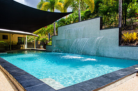 Shaded swimming pool and waterfall